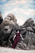 a young girl in a red dress with a black sunhat is leaning against rocks at the beach