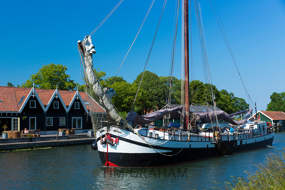 Sailing boat, former cargo boat, carrying tourists arriving along canal for a visit to Edam in The Netherlands