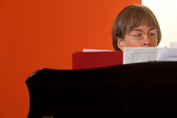 Stanford women's basketball coach, Tara VanDerveer at her home in Menlo Park, California. Playing piano.