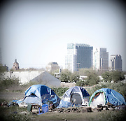 "A homeless encampment or ""tent city"" on the banks of the American River in Sacramento, CA.  The city of Sacramento is seen in the background."