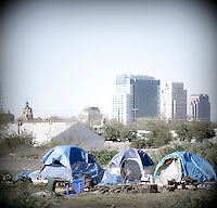 """A homeless encampment or """"tent city"""" on the banks of the American River in Sacramento, CA.  The city of Sacramento is seen in the background."""