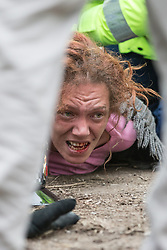 Bez at Barton Moss anti-fracking demo . Monday, 17th March 2014 .  Barton Moss , Salford , UK . A woman with blood on her face is detained by police as protesters attempt to block lorries from accessing the iGas site . Happy Mondays dancer , Bez ( Mark Berry ) , joins protesters at the Barton Moss anti-fracking protest site in Salford today (Monday 17th March 2014) . Bez has said he will stand for MP in the constituency of Salford and Eccles in 2015 . Picture by Joel Goodman/i-Images
