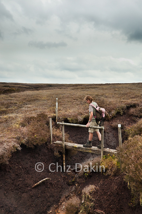 Walker crossing an uncommon bridge over the peak hags on the moorland of Hope Forest