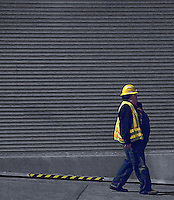 a digital painting of a worker with yellow hard hat and reflective vest walking down hill past a door with parallel horizontal lines