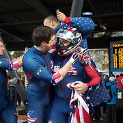 Winter Olympics, Vancouver, 2010.The USA-1 team of Steven Holcomb (centre), congratulated by team mate Steve Mesler with team mates, Curtis Tomasezicz , left and Justin Olsen, right, as they win the Gold Medal in the Bobsleigh Four-man at The Whistler Sliding Centre, Whistler, during the Vancouver Winter Olympics. 27th February 2010. Photo Tim Clayton