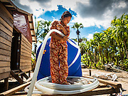 02 JUNE 2016 - SIEM REAP, CAMBODIA: A woman who helps her husband sell water unrolls a hose so her husband can refill his 3,000 litre water tank, east of Siem Reap. Cambodia is in the second year of  a record shattering drought, brought on by climate change and the El Niño weather pattern. Farmers in the area say this is driest they have ever seen their fields. They said they are planting because they have no choice but if they rainy season doesn't come, or if it's like last year's very short rainy season they will lose their crops. Many of the wells in the area have run dry and people are being forced to buy water to meet their domestic needs.    PHOTO BY JACK KURTZ
