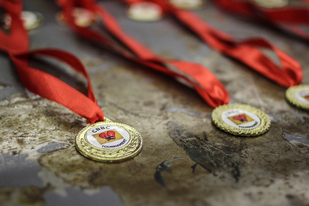 Medals of the amateur boxing tournament are put on the rusted metalliic tables made available by the commu,ity for the occasion. For some of the winenrs, a victory could mean the start of a professional career and a better life.