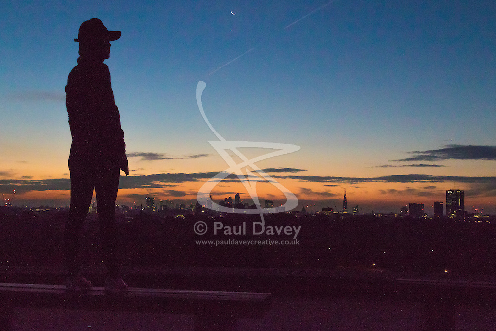 Primrose Hill, London, October 28th 2016. XA woman surveys the city skyline as dawn breaks over London.
