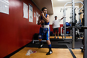 Anthony Caterina, 13, (left) shadow boxes to warm up for his first match at the Somerville Boxing Club's Fight Night at Somerville High School, as his father, Thomas Caterina (right) watches from behind him, August 21, 2015. Thomas Caterina later said that he learned that Anthony Caterina's opponent decided to forfeit the fight after watching him shadowbox.