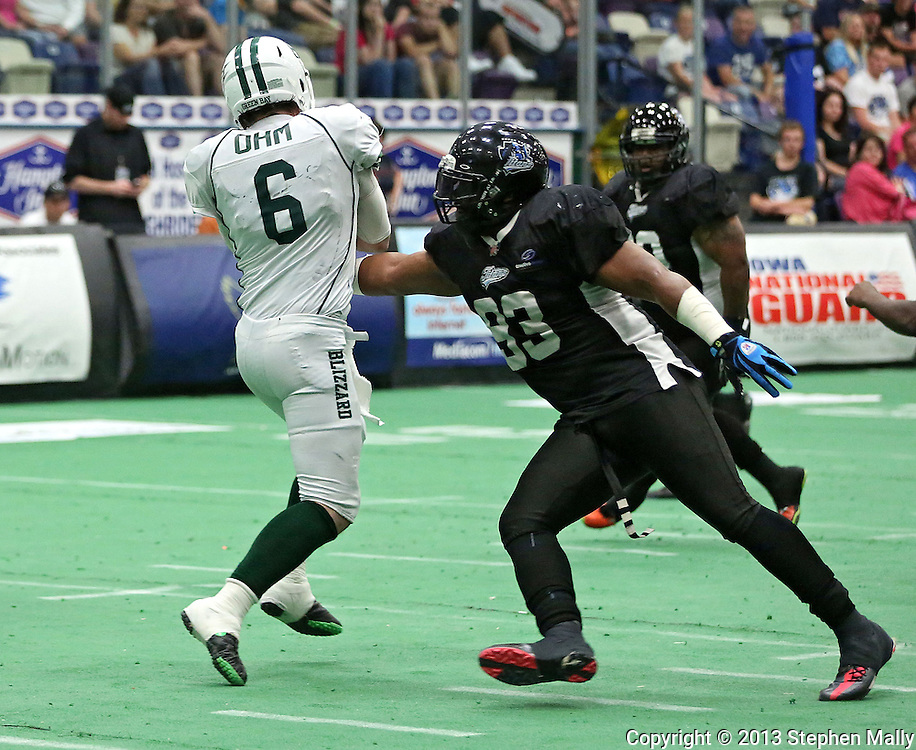 Cedar Rapids Titans defensive lineman Xzavie Jackson (93) tries to grab Green Bay Blizzard quarterback Spencer Ohm (6) during their game at the Cedar Rapids Ice Arena in Cedar Rapids on Saturday, June 8, 2013.