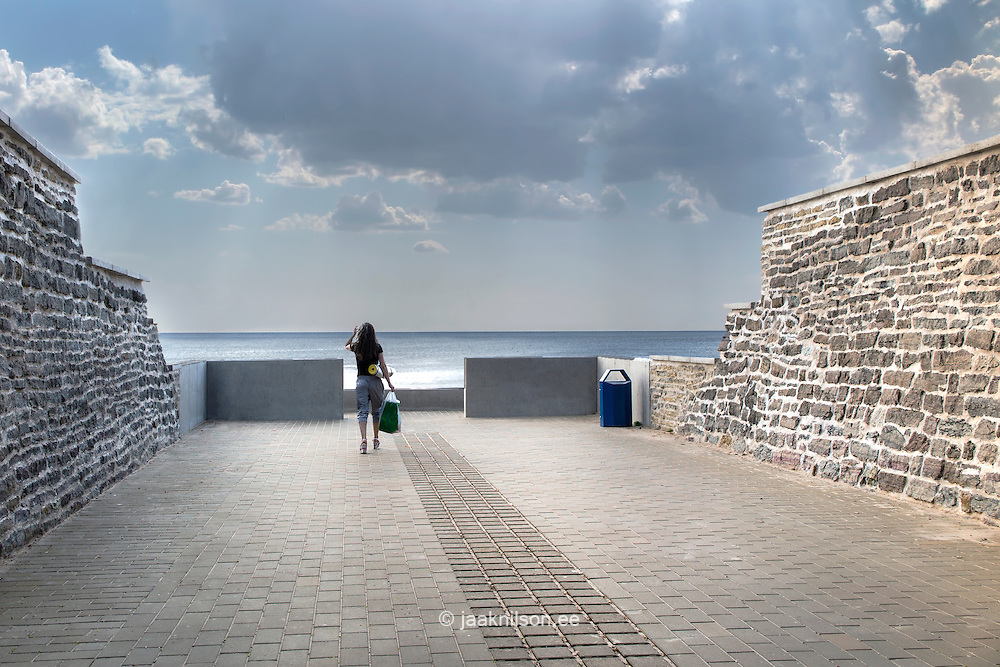 Woman figure on beach promenade in Narva-Jõesuu, Estonia. Limestone walls protecting street from sand and water. Baltic sea.
