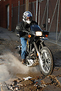 Dual sport motorcycle rider on Kawasaki KLR 650 splashing through water puddle in alleyway in downtown Oklahoma City.
