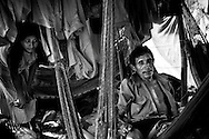 Martin Marin, 45, (right) relaxes in a hammock in the Warao indigenous community after returning from his workday at the Cambalache garbage dump in Ciudad Guayana, in northeastern Venezuela. Many Warao start salvaging recyclables, clothing and discarded food in Cambalache as early as 4am. In an effort to escape poverty, hunger and to be closer to health care facilities, approximately 300 Warao indigenous persons from the Delta Amacuro have settled in Ciudad Guayana. Although Warao community leaders say their quality of life is improved in comparison to the conditions in the Delta, the Warao are still plagued by hunger and diseases consequential of the unsanitary conditions of living and working in Cambalache.