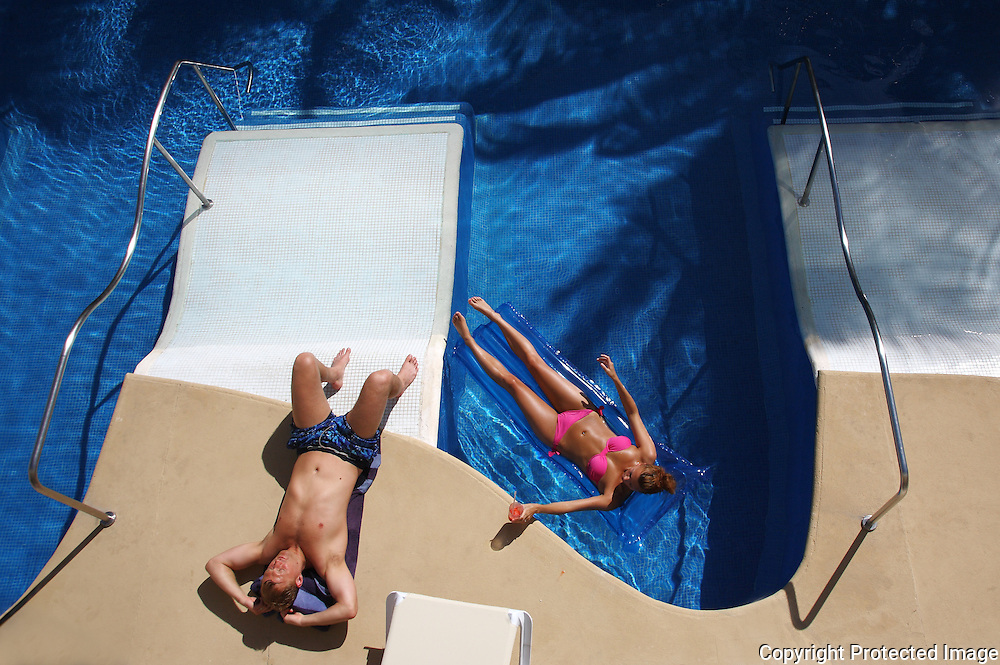 A honeymooning couple relax at the Azul Sensatori resort on the Riviera Maya, Mexico.  The all inclusive resort on the Yucatan peninsula near the Mexican town of Puerto Morelos, features swim-up rooms with sun bathing pads.