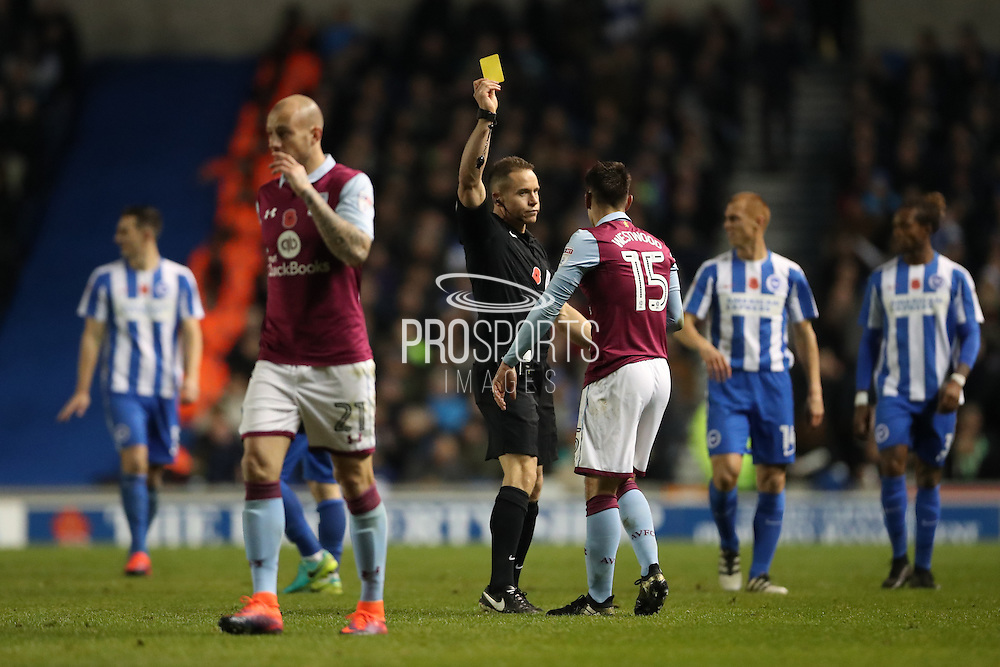 Aston Villa midfielder Ashley Westwood (15) is shown a yellow card, booked by Referee Stephen Martin during the EFL Sky Bet Championship match between Brighton and Hove Albion and Aston Villa at the American Express Community Stadium, Brighton and Hove, England on 18 November 2016.