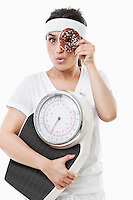 Portrait of young woman looking through donut holding weight scale over white background