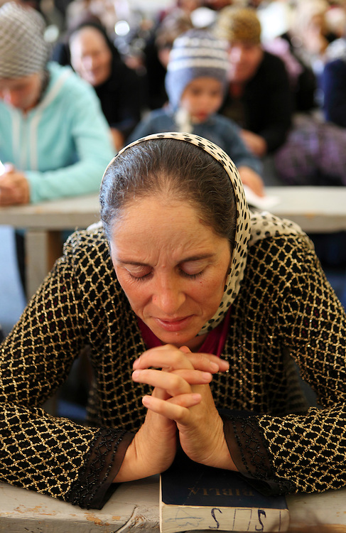 ROMa women pray during a Sunday service at the Pentecostal church in Barbulesti, Romania. 15 years ago, the population of Barbulesti, a village situated in the south of Romania and inhabited mostly by ROMa people, started to convert to the Pentecostal Church. Believers say that conversion led to a decrease in crime in the area, although official statistics do not confirm it.