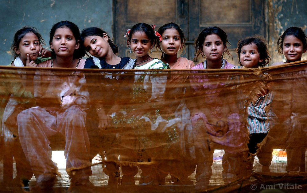 Muslim children sit inside Dariya Khan Ghhumnat Rahat refugee camp set up outside a school in the state of Gujarat in Ahmedabad, India, May 10, 2002. The extent of the damage and displacement of more than 120,000 people has threatened the secular ideals of India and left the government under attack for its inadequate relief arrangements.
