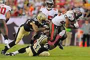 Tampa Bay Buccaneers running back Doug Martin (22) is tackled by New Orleans Saints strong safety Roman Harper (41) and strong safety Kenny Vaccaro (32) at Raymond James Stadium on Sept. 15, 2013 in Tampa, Florida. <br /> &copy;2013 Scott A. Miller