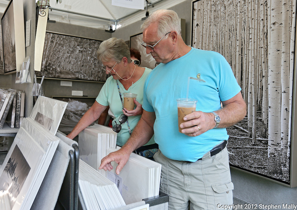 Sue Mais (from left) and her husband, Ro Mais, of Anamosa look over photography prints for sale at a booth during the 20th Annual Marion Arts Festival at City Square Park in Marion on Saturday, May 19, 2012. (Stephen Mally/Freelance)
