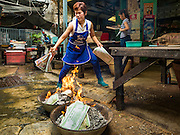 """17 AUGUST 2016 - BANGKOK, THAILAND: A woman burns """"ghost money"""" in front of her home during the Ghost Festival in the Chinatown section of Bangkok. The Ghost Festival is a Buddhist and Taoist holy day celebrated on the 15th day of the 7th lunar month. It is primarily celebrated in China and Chinese communities beyond China. In Thailand, it's celebrated in Thai-Chinese communities in Bangkok, Phuket and Chiang Mai.  On that day ghosts and spirits, including those of the deceased ancestors, come out from the lower realm to visit the living. Families prepare elaborate banquets for the spirits and burn """"ghost money"""" for the spirits to use in the other realm. It is a day for venerating dead relatives.     PHOTO BY JACK KURTZ"""