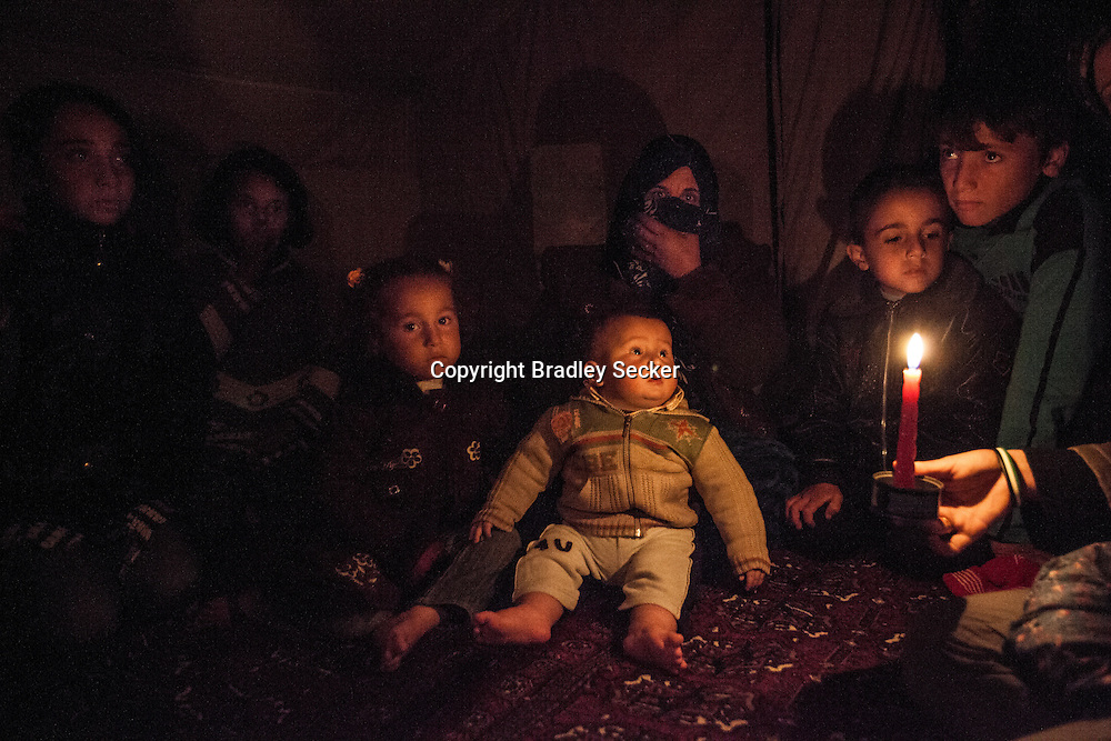 Ebtisam Hammud, centre, holds her young son Ahmed, in their tent lit on ly by candle light and without electricity or heating in Atmeh camp. More than 12,000 dieplaced Syrians currently live in the camp. 02/01/2013 Bradley Secker for Helsingin Sanomat