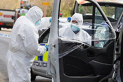 © Licensed to London News Pictures . 30/04/2013 . Salford , Greater Manchester , UK . Forensic examiners wrap one of the prison van's doors with a smashed window . Police and forensic scenes of crime examiners at the scene on Regent Road , Salford , where a prison van was hijacked this morning (Tuesday 30th April) . Police report that two prisoners escaped . Photo credit : Joel Goodman/LNP