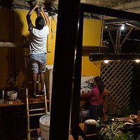 Antonio Cruz Sanchez, 26, works on wiring new low wattage lights in the communal kitchen at the SERES Embassy, where he works and lives. Beside him, Abigail Quic, his co-worker and housemate, cooks dinner for everyone. San Juan Del Obispo, Guatemala, July 23, 2014
