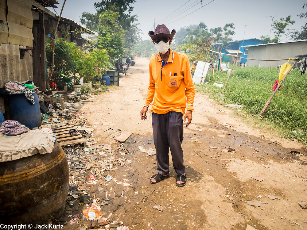 17 MARCH 2014 - PHRAEKSA, SAMUT PRAKAN, THAILAND:  A resident of a landfill wears a breathing mask because of the smoke coming off of a fire buring in the landfill. A fire apparently spontaneously started in the landfill in Samut Prakan over the weekend and threatens the homes of workers who live near the landfill. The fire Officials said the fire started when garbage in the landfill burst into flames and the flames were spread by hot, dry winds. Hundreds of people have been evacuated because of the fire and acrid smoke from the fire has spread as far as Bangkok. It hasn't rained in central Thailand in more than three months, impacting agriculture and domestic water use. Many farms are running short of irrigration water and salt water from the Gulf of Siam has come up the Chao Phraya River and infiltrated the water plants in Pathum Thani province that serve Bangkok.  PHOTO BY JACK KURTZ