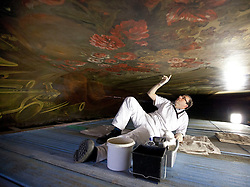 "© Licensed to London News Pictures. 04/03/2013. London, UK. On top of a scaffolding tower at around 40 feet in the air, restoration expert Francesco Rosellini examines damage to enamel during restoration work on the ceiling of the 'Painted Hall' at Greenwich Old Naval College in London today (04/03/2013). The conservation work, paid for by the Heritage Lottery Fund (HLF), is the 10th time the Painted Hall (often described as ""finest dining hall in Europe"") will have been restored since its completion in 1784 and will have taken around five months to complete when the hall is unveiled to the public in May of this year. Photo credit: Matt Cetti-Roberts/LNP"