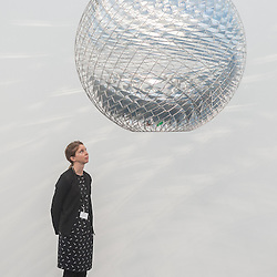 London, UK - 15 October 2014: a woman looks at 'Schools of Movement sphere 2014' by Olafur Eliasson during the first day of Frieze Art Fair and Frieze Masters in Regent's Park.