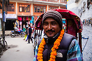 A rickshaw driver wears a flower garland as he awaits customers for a rickshaw drive through the narrows streets of the Thamel District in Kathmandu, Nepal.