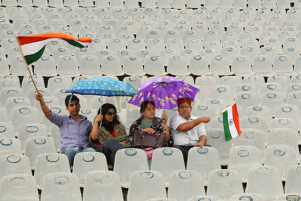 Fans wait for the rain to stop during day 1 of the 3rd Airtel Test Match between India and Australia held at the PCA Stadium, Mohal, India on the 14th March 2013..Photo by Ron Gaunt/BCCI/SPORTZPICS ..Use of this image is subject to the terms and conditions as outlined by the BCCI. These terms can be found by following this link:..http://www.sportzpics.co.za/image/I0000SoRagM2cIEc