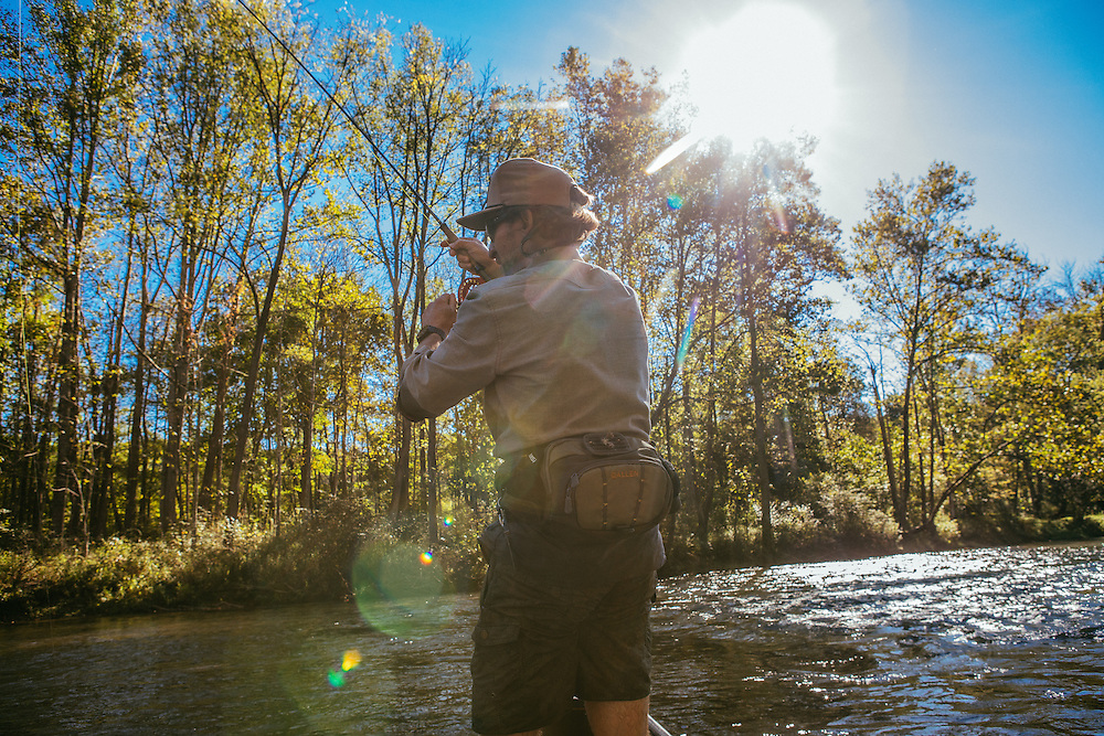 Man fishing with dog from canoe and in the Jackson River stream for rainbow trout in Virginia in the Blue Ridge Mountains.