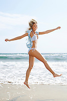Young woman in bikini on beach running and jumping portrait side view