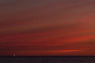 Zonsondergang bij de Waddenzee met in de verte uitzicht op Terschelling.