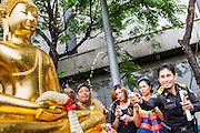 12 APRIL 2013 - BANGKOK, THAILAND:   Thais sprinkle scented oils on the Phra Buddha Sihing while it is paraded through the streets of Bangkok on the first day of Songrkran. The Phra Buddha Sihing, a revered statue of the Buddha, is carried by truck through the streets of Bangkok so people can make offerings and bathe it in scented oils. Songkran is celebrated in Thailand as the traditional New Year's Day from 13 to 16 April. The date of the festival was originally set by astrological calculation, but it is now fixed. If the days fall on a weekend, the missed days are taken on the weekdays immediately following. Songkran is in the hottest time of the year in Thailand, at the end of the dry season and provides an excuse for people to cool off in friendly water fights that take place throughout the country. The traditional Thai New Year has been a national holiday since 1940, when Thailand moved the first day of the year to January 1. The first day of the holiday period is generally the most devout and many people go to temples to make merit and offer prayers for the new year..  PHOTO BY JACK KURTZ
