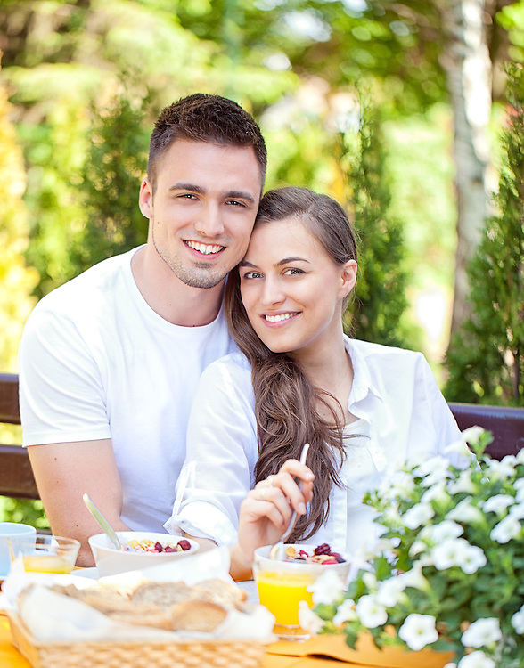 Young romantic couple having breakfast in their garden.