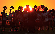 The Knightstown Junior Varsity hold up their helmets as the sun sets after their final game of the 2012 season at Eastern Hancock High School.