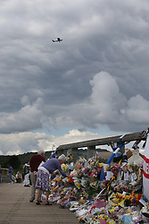© Licensed to London News Pictures. 02/09/2015. Shoreham, UK. A light aircraft passes overhead as people look at floral tributes placed on a bridge near the site of the crashed Hawker Hunter fighter jet. The aircraft crashed while performing at the Shoreham air show on August 22, 2015 killing 11 people on the ground. As an inquest into the deaths opened today in nearby Horsham, the name of the last of the victims Graham Mallinson was released.  Photo credit: Peter Macdiarmid/LNP