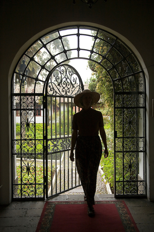 South America, Ecuador, Lasso, woman in arch with wrought-iron door to garden, Hacienda La Cienega  MR