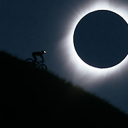 Andrew Whiteford mountain bikes with his light on underneath the 2017 eclipse during totality for this in-camera double exposure taken on August 21, 2017.