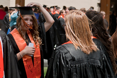 Lathan Goumas | MLive.com..Amanda Adkins, 18, holds her graduation cap to her head as the wind blows before the 2012 Flushing High School commencement ceremony at the Whiting Theater in Flint, Mich. on Sunday June 3, 2012.