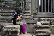 A tourist sits on a stone wall and looks her photos on her digital camera within the temple of Angkor Wat Siem Reap, Cambodia.  Angkor Wat is Cambodia's main tourist destination and one of UNESCO's world heritage sites. <br /> (photo by Andrew Aitchison / In pictures via Getty Images)