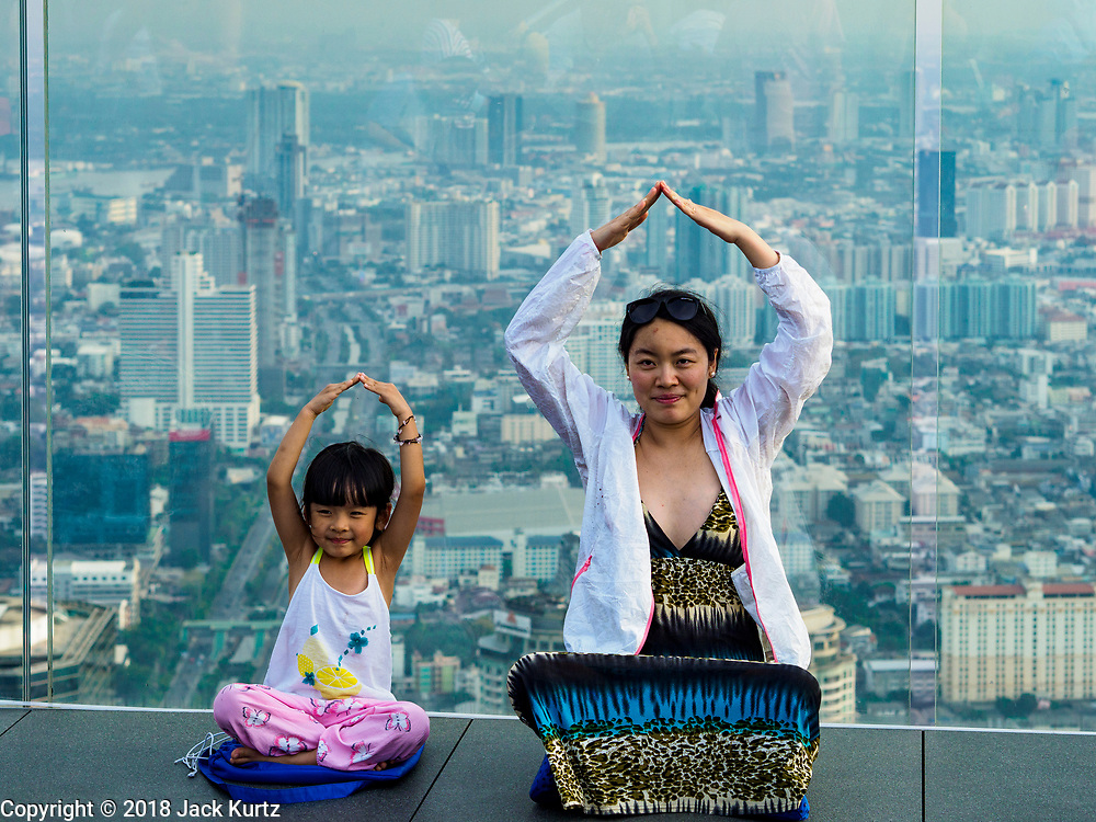 """27 DECEMBER 2018 - BANGKOK, THAILAND:  People on the """"glass tray,"""" a glass overlook that sticks out over the south edge of the Maha Nakhon Tower. The MahaNakhon Skywalk, at the top of the King Power Maha Nakhon Tower, is 1,030 feet (314 meters) above street level. It is the tallest building and highest vantage point in Bangkok. The skywalk opened in November and has been drawing large crowds.    PHOTO BY JACK KURTZ"""