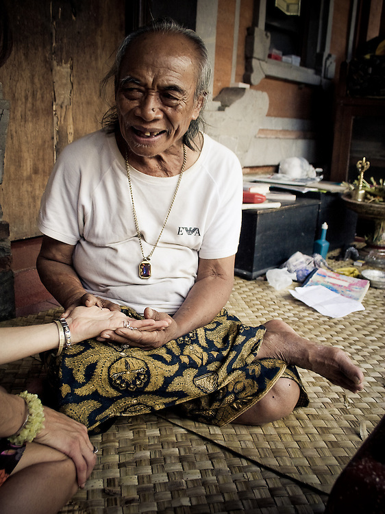 Ketut Liyer, of Eat, Pray, Love fame, holds the palm of a western woman on his front porch in Ubud, Bali, Indonesia.
