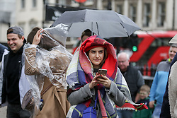 © Licensed to London News Pictures. 01/11/2019. London, UK. A woman covers her head during light rainfall on a milder November day in Westminster, London. Photo credit: Dinendra Haria/LNP