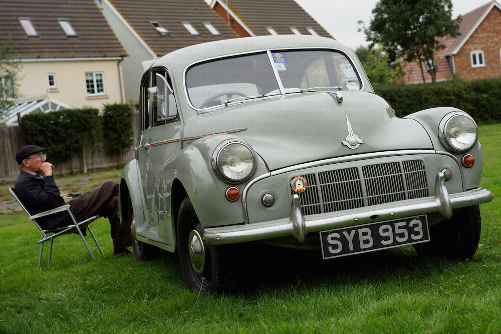 Morris Minor car made in Great Britain in 1953 with split screen. Male figure sitting  behind eating a picnic.