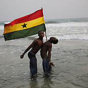 Young men proudly play with the Ghana flag in the sea. Accra, Ghana