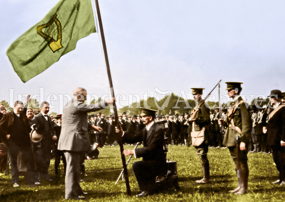 Irish Parliamentary Party leader John Redmond presents a flag to a kneeling volunteer at a rally of the Redmondite Irish National Volunteers c. 1914-15. Location unknown. (Part of the Independent Newspapers Ireland/NLI Collection) Colourised by Tom Marshall (PhotograFix).